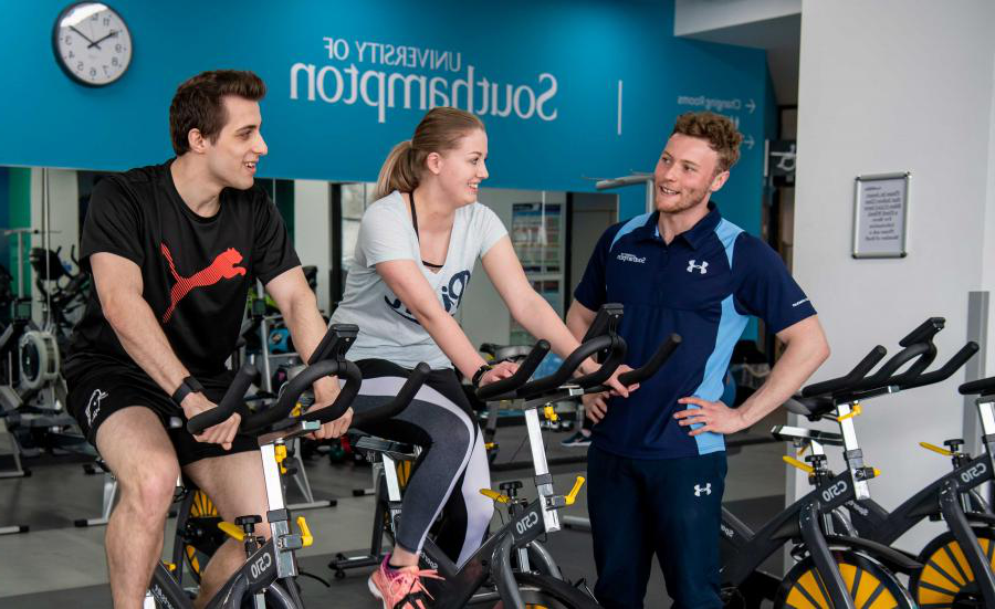 Two students working out on exercise bikes in a gym, assisted by a personal trainer.