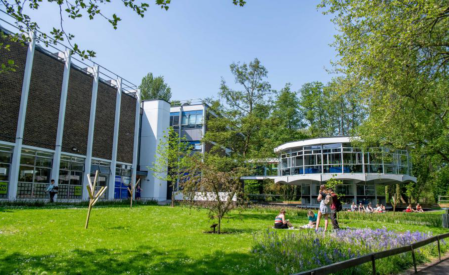 Modern looking campus building with, students relaxing on a grassy area in the foreground.