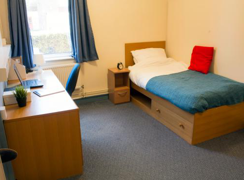 A spacious bedroom. The floor is blue carpeted and a neatly made single bed is visible against one wall. On the other side of the room is a wooden desk with office chair and a large window.