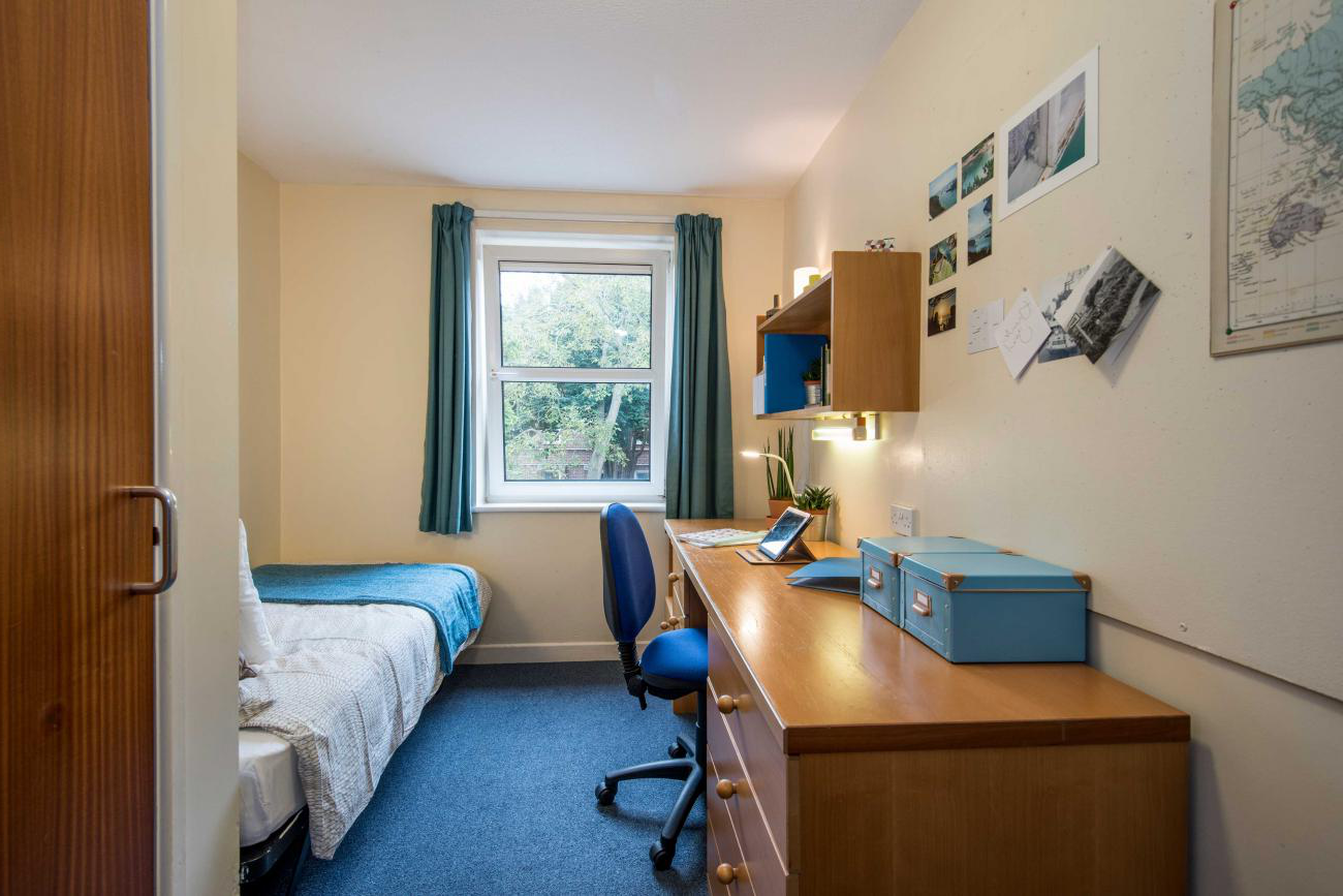 A bright, airy student bedroom with desk and single bed.