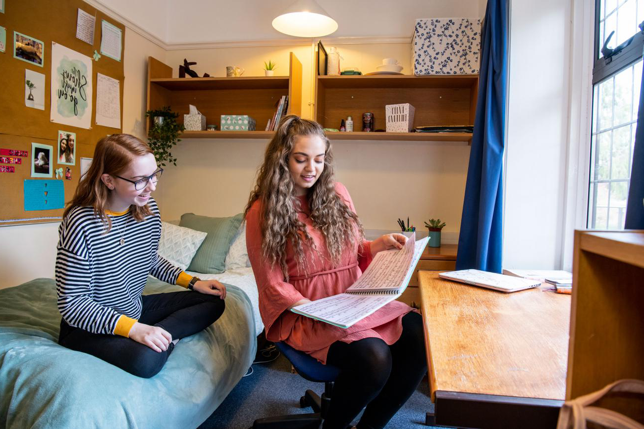 Two students sat in a bedroom talking and looking at books and notes. Light streams in through a large window.