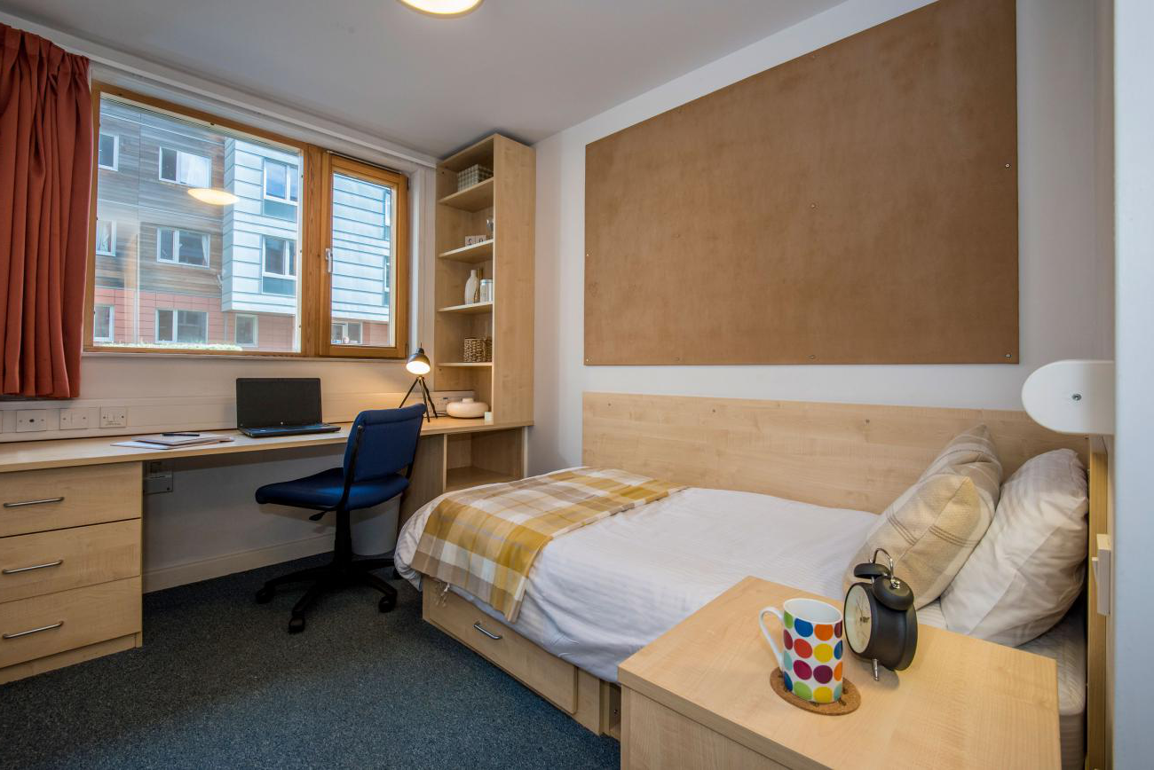 An empty student bedroom containing a neatly made single bed and a large desk with chair, beneath a window.