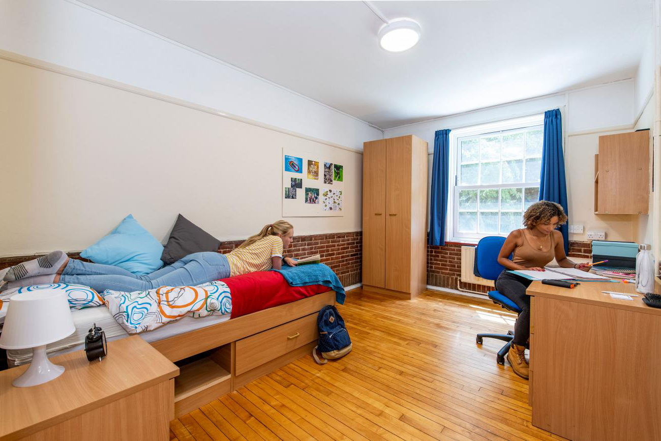 A spacious student bedroom with wooden floor and large window. One student lays on the bed reading a book, another sits working at the desk.
