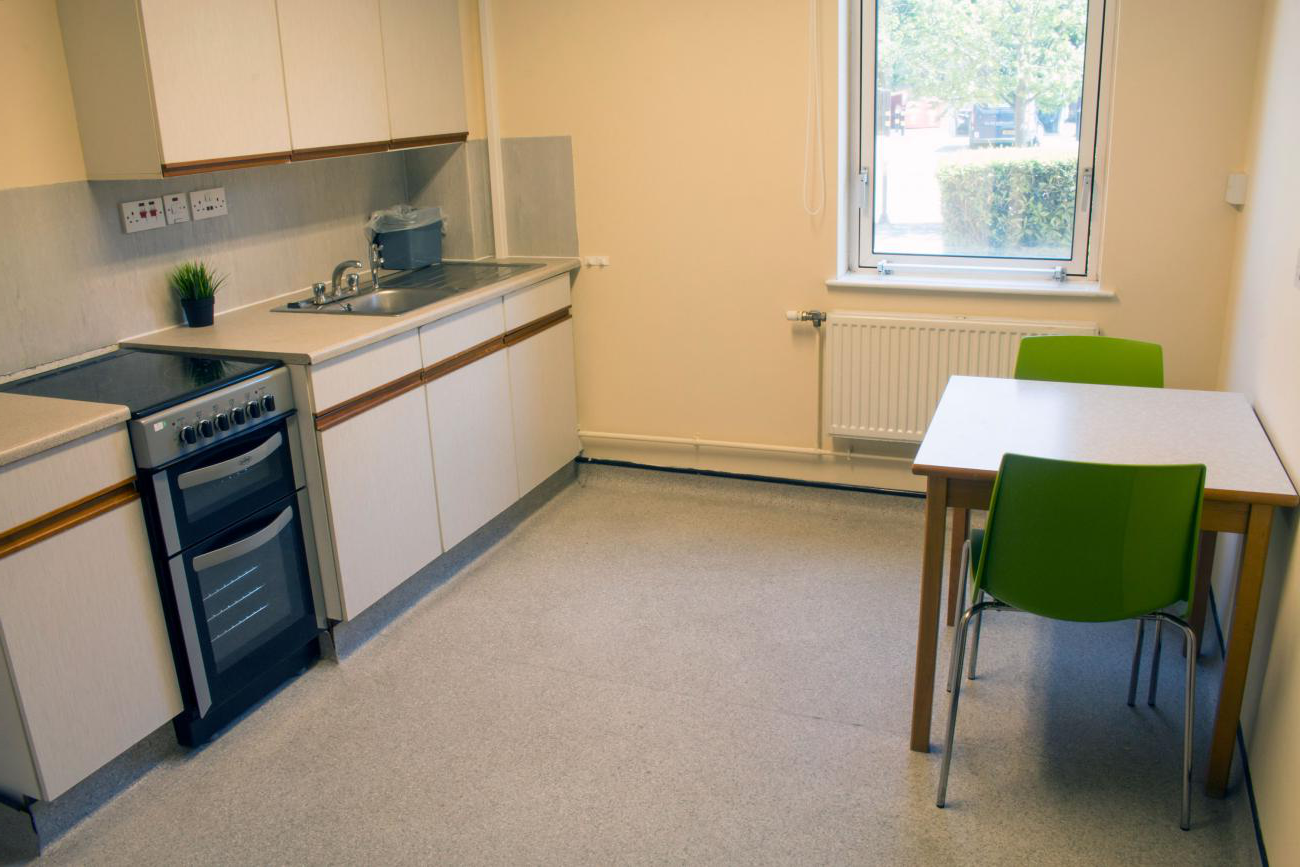 A large kitchen with laminate flooring. It contains modern looking kitchen appliances and cupboards, a small square table with two chairs and a window.