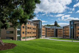 Exteri要么 shot of grassy courtyard and student accommodation blocks on a sunny day.